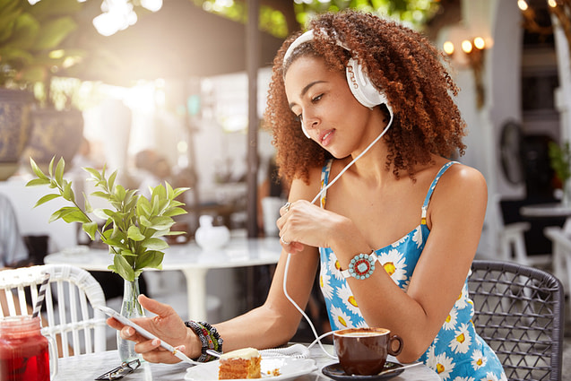 Satisfied African American female looks positively in smart phone, chats online and browses website,
