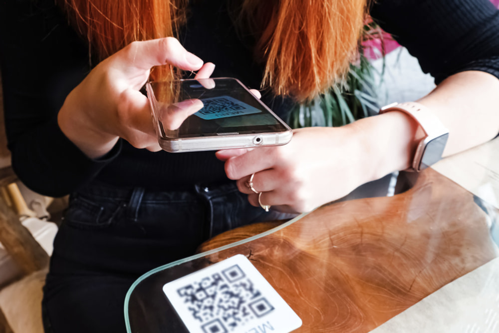 Woman scanning the barcode qr code in restaurant