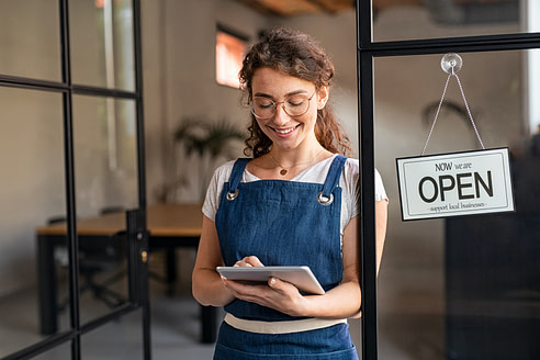 Small business owner using digital tablet at entrance
