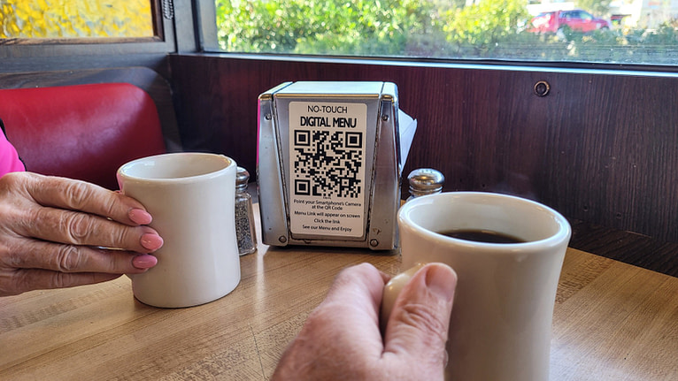 Drinking coffee while waiting for food and getting ready to scan digital menu with cellphone.
